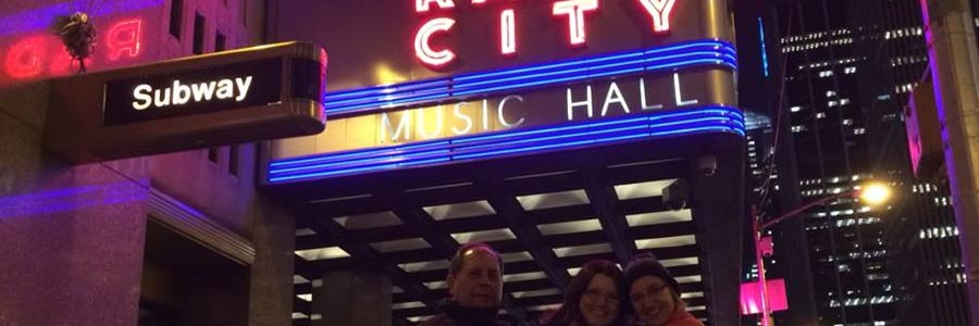 people posing under Radio City Music Hall sign in NYC